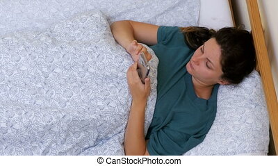 Top view of a Woman using a smartphone lying on a white bed in the morning