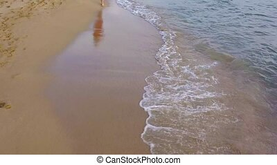 Top view of a woman walking barefoot along wet sand beach. Running wave is washing away footprints on the sand