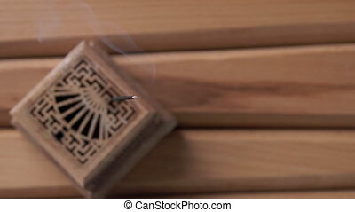 Top view of a wooden box with a burning incense stick. On...