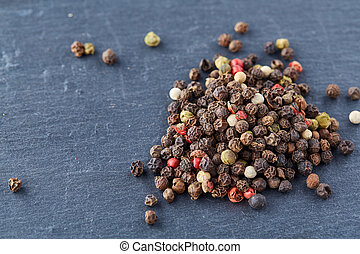 Top view of a wooden spoon full of allspice seeds isolated on dark background, shallow depth of field, front focus
