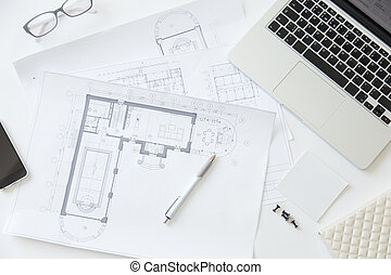 Top view of a working desk with an architect drawing