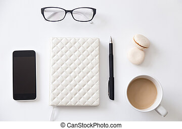 Top view of a working desk with notebook, phone, coffee