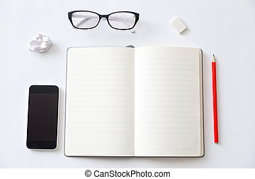 Top view of a working desk with open blank notebook