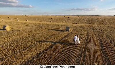 top view of a young couple walking in a field at sunset