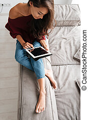 Top view of a young woman in sweater using pc tablet