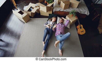 Top view of adorable young couple lying on floor of their new apartment in bedroom, talking then kissing and hugging. Carton boxes, guitar, carpet and bed are visible.