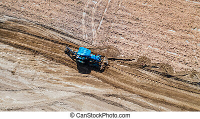 Top view of agricultural tractor vehicles working at field