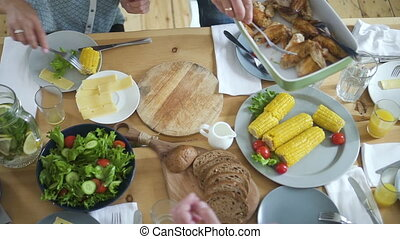 Top view of american family serving food sitting at festive desk in home.