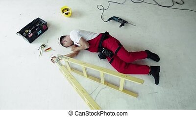 Top view of an injured man lying on the floor after an...