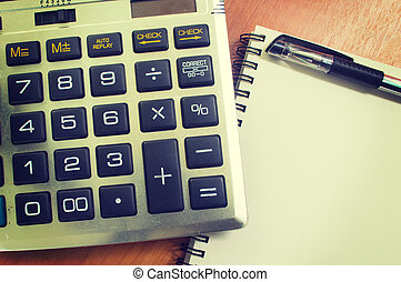 top view of an office wooden desktop with calculator and pen