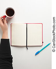 Top view of an open blank red notebook in the center, a blue pen beside it and a female hand holding a red cup of coffee in white background, with space for text