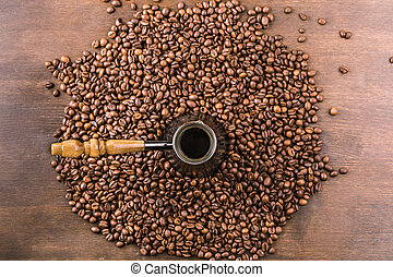 top view of aromatic coffee beans and turk on wooden tabletop