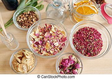 Top view of aromatic stuff in bowls on table prepared for soap making process