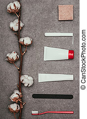 top view of arrangement of various feminine hygiene supplies and cotton twig on grey surface