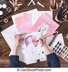 top view of artist making sketches with watercolor paints