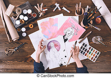 top view of artist painting with watercolor paints