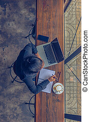 Top view of Asian woman working on laptop , cellphone , cappuccino