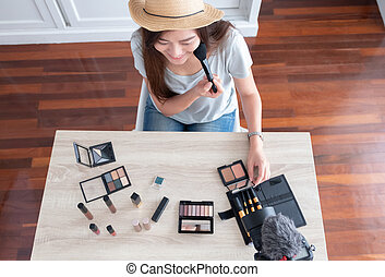 Top view of Asian young female blogger recording vlog video with makeup cosmetic at home online influencer on social media