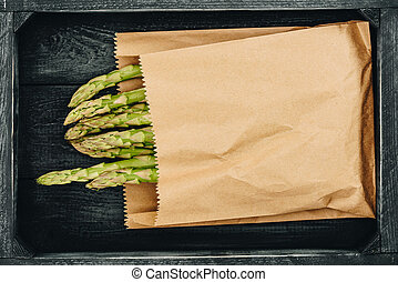 top view of asparagus in shopping paper bag