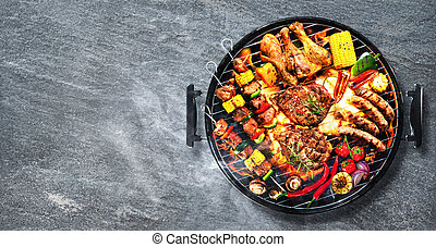 Top view of assorted delicious grilled meat with vegetables on barbecue on rustic stone background