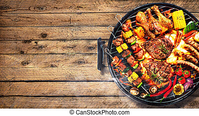 Top view of assorted delicious grilled meat with vegetables on barbecue on rustic wooden planks