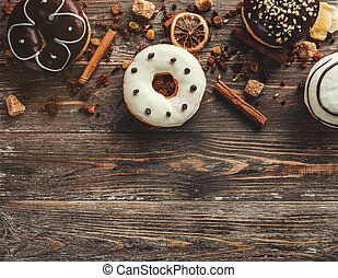 Top view of assorted donuts on wooden background with copy space. Selective focus with effects
