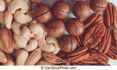 Top view of macadamia, cashews and brazil nuts on a gray background, close, flat lay