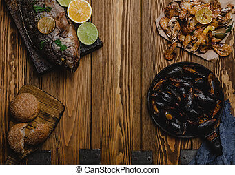 Top view of assorted seafood and baked fish with bread on wooden table
