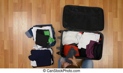 Top view of attractive woman standing on wooden floor and unpacking clothes from suitcase