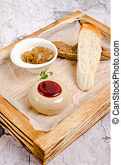 top view of baguette with French pate and marinated. Homemade chicken pate in glass jar and toast bread on wooden rustic kitchen board. Gray background