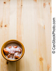 Top view of banana with syrup and coconut milk in brown bowl on wooden background, Thai dessert.