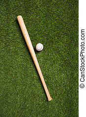 top view of baseball bat and ball on grass field