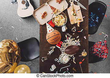 Top view of basketball ball with funny face on messy table after party