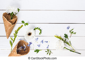 Top view of beautiful blossom flowers and green leaves in waffle cones on wooden table