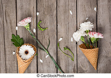 Top view of beautiful flowers in waffle cones and petals on wooden background