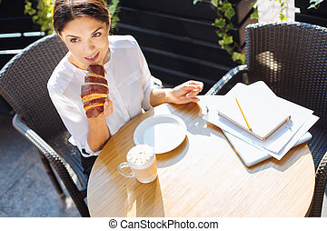 Top view of beautiful woman eating croissant in cafe - I...