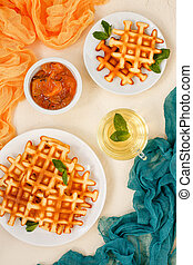 Top view of Belgian waffles on beige table.