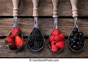 Top view of berries mixed (strawberries, raspberries, blueberries and blackberries) on vintage metal spoons over dark wood. Agriculture, Gardening, Harvest Concept. Background with space for text.