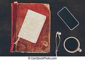 top view of bible with smartphone and cup on wooden table