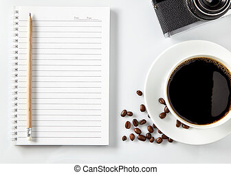 Top view of black coffee and blank notebook