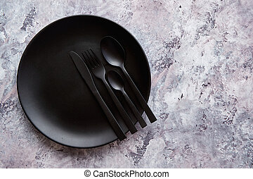 Top view of black empty plate on marble stone background -...