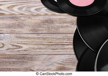 Top view of black vinyl records on brown wooden background. Retro toned. Copy space