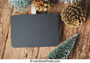 Top view of blank blackboard with xmas tree and gold pine cone on grunge wood table .winter holiday greeting card. space for display of design or content.