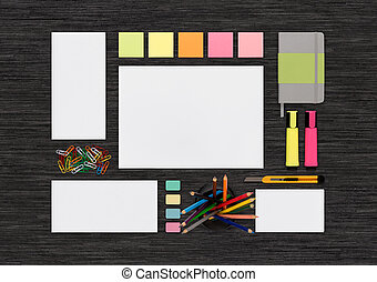 Top view of blank colorful stationery mock up on black office de