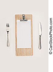 blank paper on clipboard and cutlery
