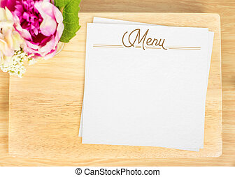 Top view of Blank wooden plate with white menu card and flower pot on table top,Mock up for adding your design, Clipping path on paper card