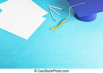 Top view of blue graduation cap and paper