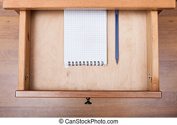 blue pen and squared notebook in open drawer