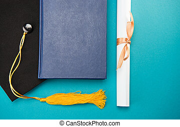 Top view of book, graduation cap and diploma on blue, education concept