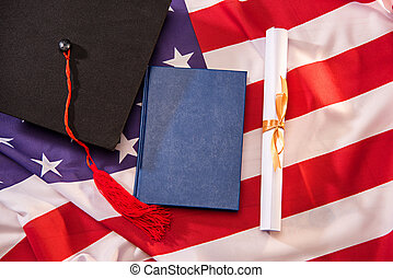 Top view of book, graduation cap and diploma on american flag, education concept